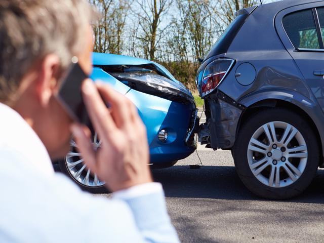 A man is seen on the phone with a car accident lawyer after being in a car wreck.