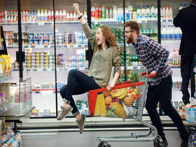 a young woman rides in a shopping cart as a young man pushes her.