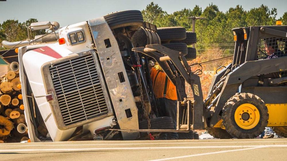 A wrecked semi-truck lays in the road with spilled lumber. Las Vegas truck accident lawyers can prove negligence by the trucker caused the accident.