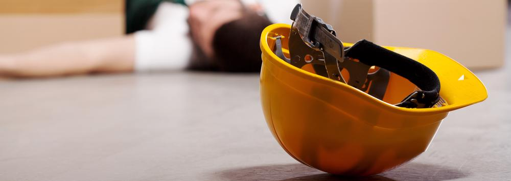 A worker lies on the ground in the background with his hard hat in the foreground after a personal injury at work.