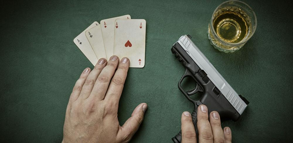 A man sits at a poker table with four aces, a glass of scotch, and a gun on the table. Las Vegas premises liability attorneys can fight for those injured on their casino property.