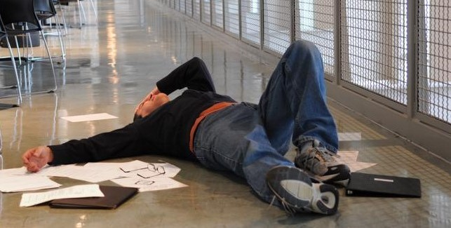 A man lies on the ground after a slip & fall injury.