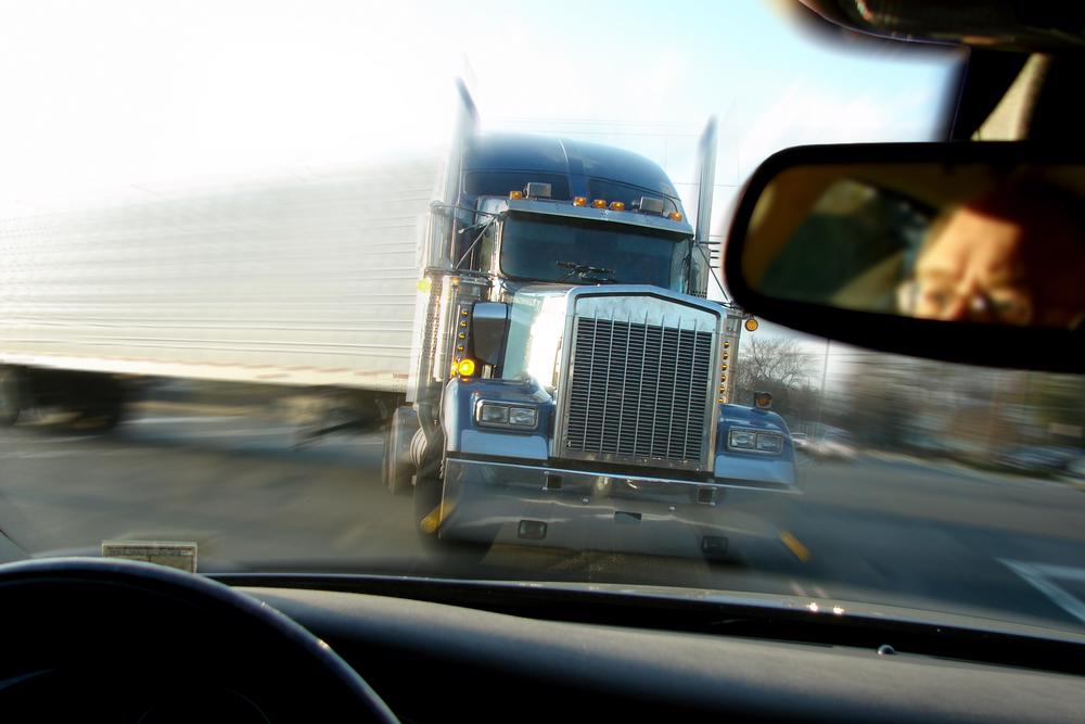 A semi truck is seen about to collide head on with a car.