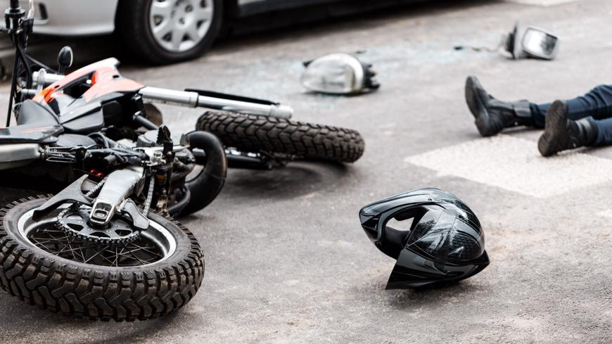 A motorcycle and helmet lying on the pavement after an accident.