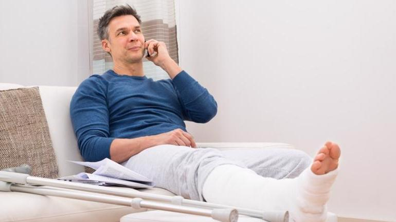 A man with an injured leg speaking on the phone.