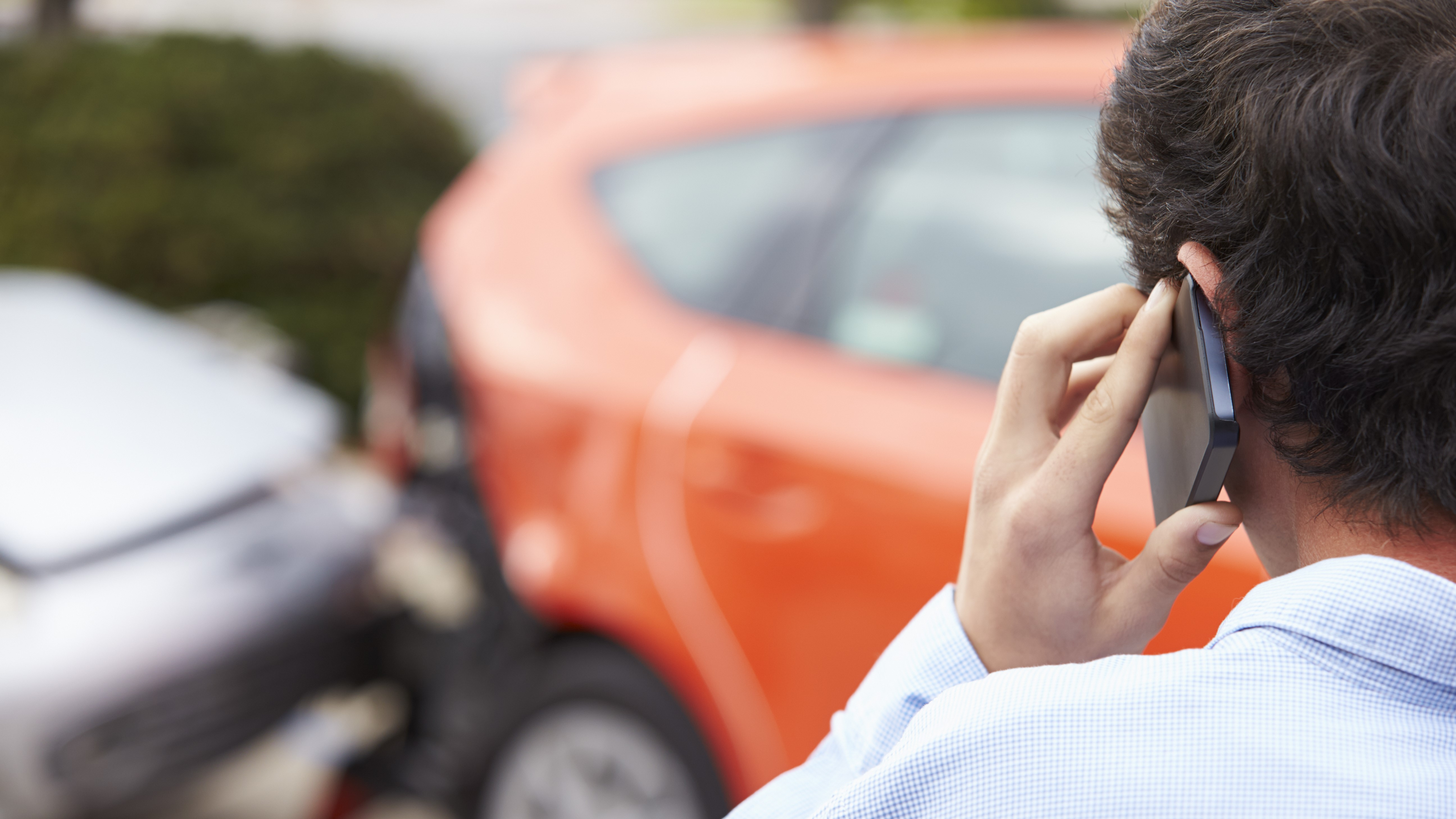 A man on the phone after a car accident.