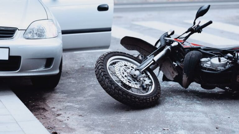 A motorcycle lying on the ground after an accident with a car