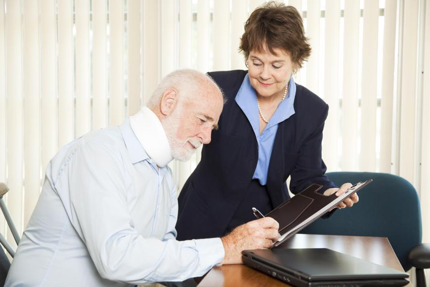 A man signing a personal injury claim settlement.