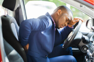 Man with Car Accident Injury Causing Back Pain While Driving